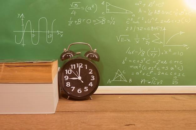 Szkolne książki i zegar na biurku z zieleni deską, edukaci pojęcie