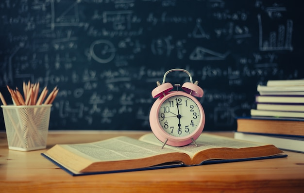Szkolne książki na biurko formułach i physics inskrypcja na blackboard
