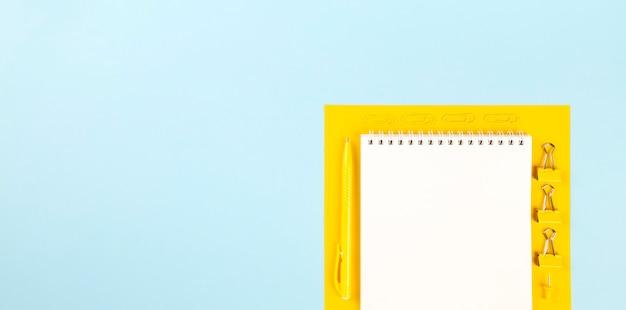 Szkolne materiały biurowe na niebieskim i żółtym tle. powrót do koncepcji szkoły. kompozycja geometryczna i monochromatyczna. widok z góry. skopiuj miejsce