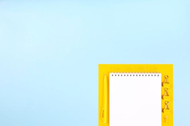 Szkolne materiały biurowe na niebiesko-żółtej ścianie. powrót do koncepcji szkoły. kompozycja geometryczna i monochromatyczna. widok z góry. skopiuj miejsce