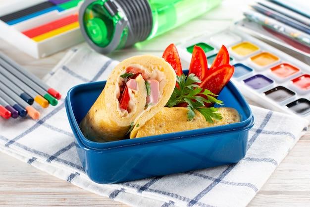 Szkolne obiady i artykuły papiernicze na stole. pojemnik na lunch ze zdrowym obiadem