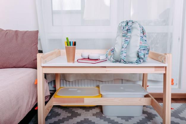 Szkolne przybory na szkolnej ławce. niebieski plecak, białe słuchawki, notatnik i długopisy w słoiku leżały na białej szkolnej ławce.