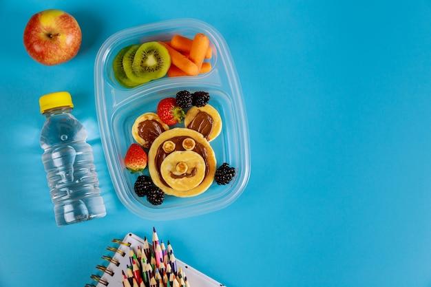 Szkolne pudełko na lunch dla dzieci z zabawnymi naleśnikami z owocami i marchewką.