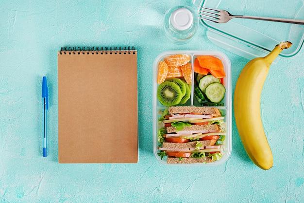 Szkolne pudełko na lunch z kanapkami, warzywami, wodą i owocami na stole.
