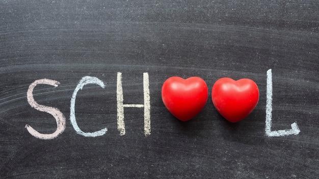 Szkolne słowo z dwoma czerwonymi symbolami serca odręcznie na tablicy