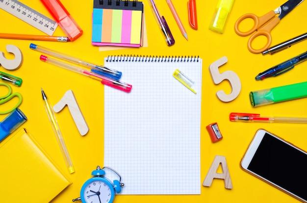 Szkolni akcesoria na biurku na żółtym tle. koncepcja edukacji. materiały biurowe.