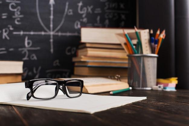 Szkolny biurko w sala lekcyjnej z książkami na tle kredowa deska z pisać formułami