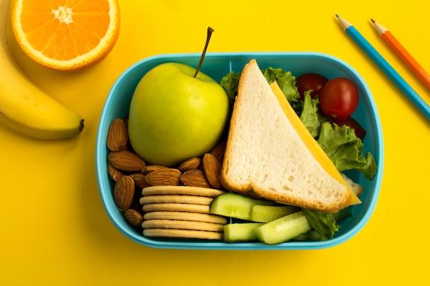 Szkolny lunch w pudełku na żółtym tle odgórny widok.