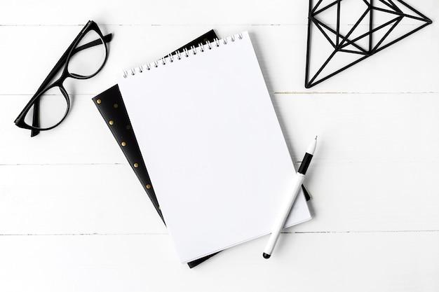 Szkolny notatnik z szkłami i kawą na drewnianym tle
