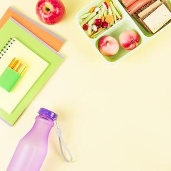 Szkolny pojemnik na drugie śniadanie i artykuły papiernicze na pastelowym pulpicie, miejsce na kopię