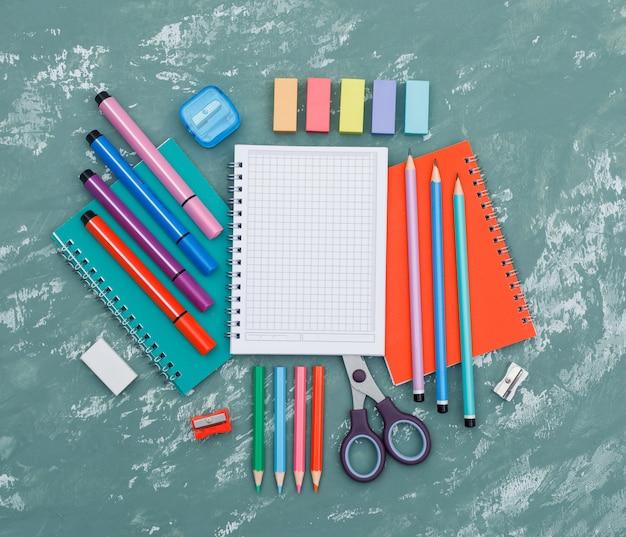 Szkolny ponownie otwierać pojęcie z notatnikami, szkolne dostawy na tynku tła odgórnym widoku.