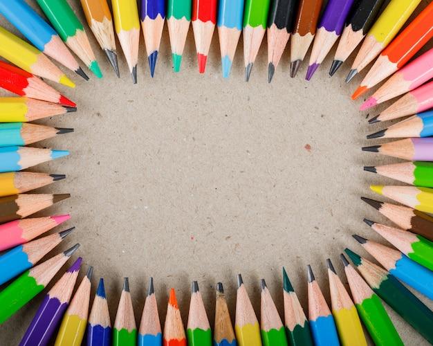 Szkoły i wyposażenia pojęcie z barwionymi ołówkami na papierze.