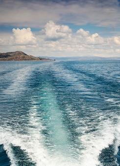 Szlak łodzi z pienistymi falami za szybką motorówką i niesamowitymi chmurami nad jeziorem titicaca w peru