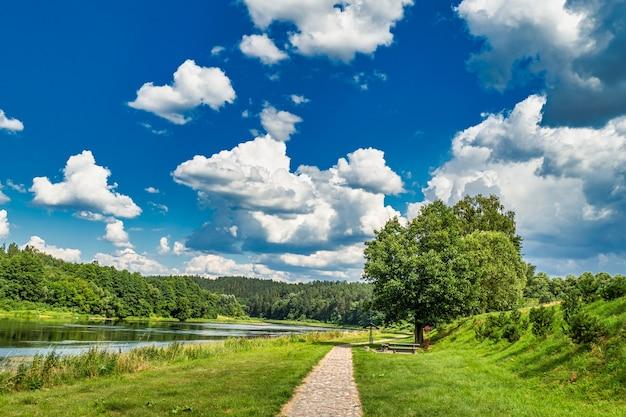 Szlak turystyczny z pięknym krajobrazem rzeki i lasu.