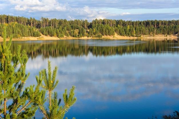 Szmaragdowe jezioro z teksturowymi chmurami, piaszczystymi górami i lasem. widok z wysokiej góry. kazań, rosja.