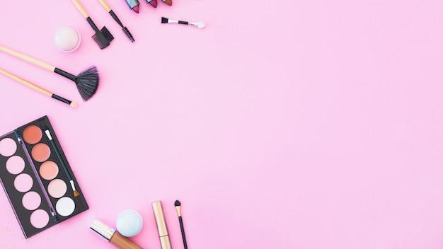 Szminka; pędzle do makijażu i palety na różowym tle