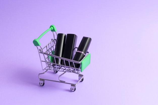 Szminki w czarnych etui umieszczone są w wózku sklepowym na jaskrawym neonowy fiolet