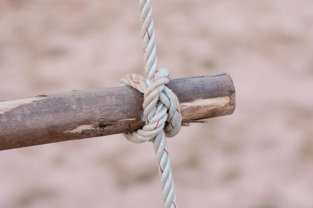 Sznur jest zawiązany w węzeł wokół słupka ogrodzeniowego, słup drewna związany węzłem liny