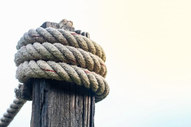 Sznur kotwiczny wiąże drewniany słup