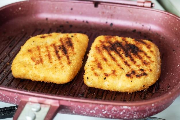 Sznycel smażony na patelni grillowej. dwa kawałki cordon bleu z szynką i serem na patelni.