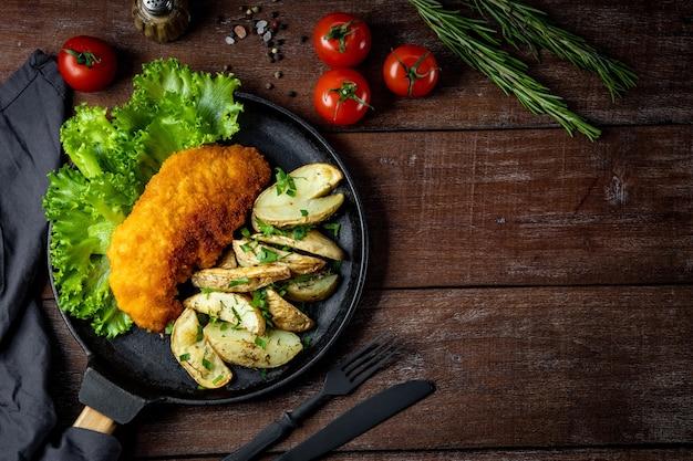 Sznycel wieprzowy z pieczonymi ziemniakami na patelni