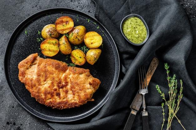 Sznycel z kurczaka smażonego z pieczonymi ziemniakami. czarne tło. widok z góry