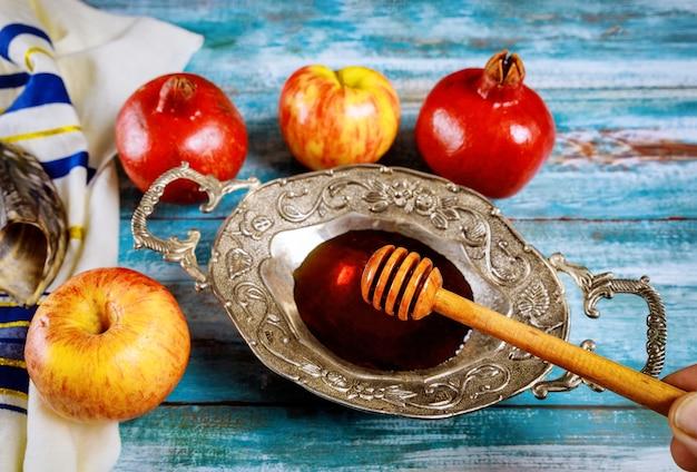 Szofar i talit ze szklanym słojem miodu i świeżymi dojrzałymi jabłkami. symbole żydowskiego nowego roku.
