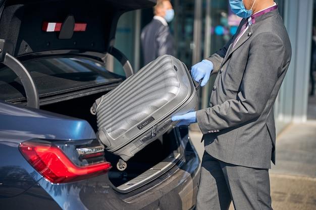 Szofer w garniturze pakuje bagaż do samochodu w pobliżu terminalu lotniska, mając na sobie maskę ochronną i rękawiczki