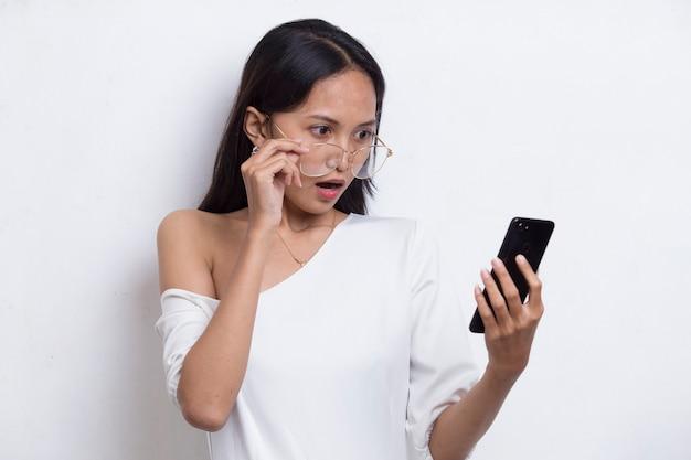 Szok młoda azjatycka piękna kobieta korzystająca z telefonu komórkowego na białym tle