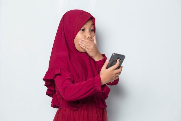 Szoku muzułmańskiej azjatykciej małej dziewczynki używającej smartfona na białym tle