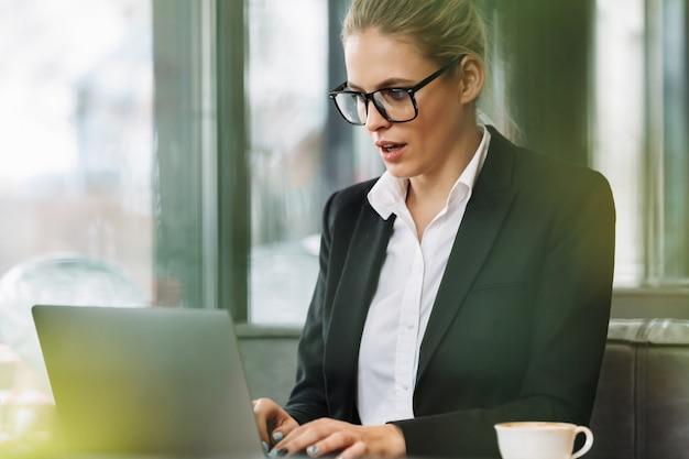 Szokująca blondynki biznesowa kobieta używa laptop