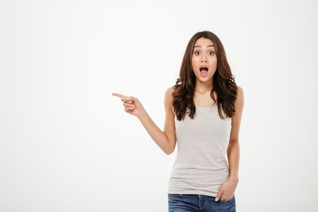 Szokująca brunetki kobieta wskazuje na copyspace i patrzeje kamerę nad popielatym z ręką w kieszeni