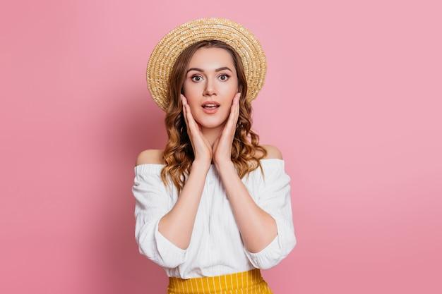 Szokująca caucasian dziewczyna w słomianym kapeluszu i białej rocznik sukni odizolowywającej na różowej ścianie. zaskoczony podekscytowana dziewczyna koncepcja baner sprzedaż internetowa