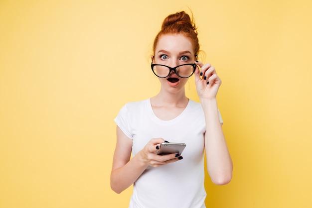 Szokująca imbirowa kobiety mienia smartphone i patrzeć przez okularów