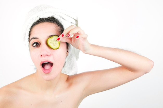 Szokująca młoda kobieta trzyma ogórkowego plasterek nad ona oczy odizolowywający na białym tle