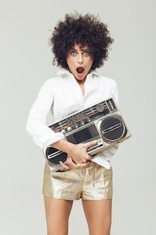 Szokująca retro kobieta trzyma boombox.