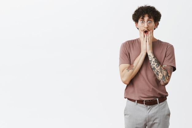 Szokująca wiadomość odsuwa faceta od kolan. portret zaskoczonego, zdumionego, przystojnego mężczyzny z kręconymi włosami z tatuażami na ramionach z opuszczoną szczęką trzymającego dłonie pod ustami, wpatrującego się pod wrażeniem