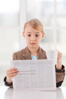 Szokujące wiadomości. zaskoczona mała dziewczynka w formalnym stroju czyta gazetę i trzyma kubek siedząc przy stole