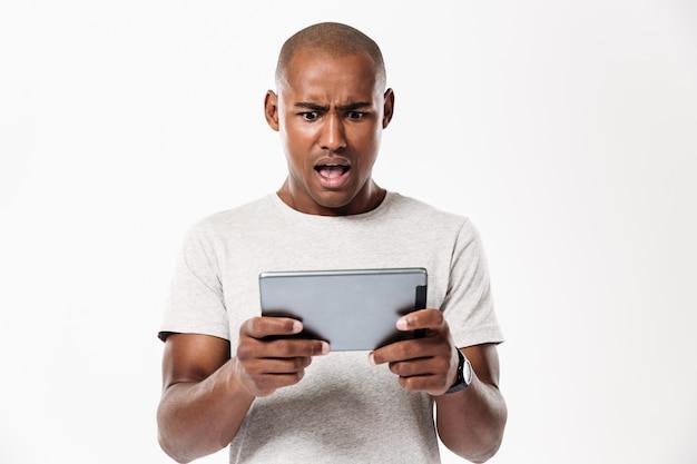 Szokujący afrykański mężczyzna używa pastylka komputer