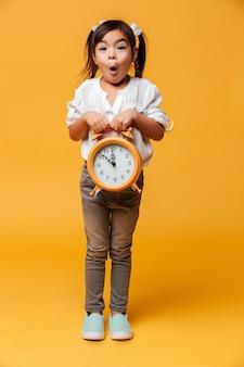 Szokujący małej dziewczynki dziecko trzyma zegarowego alarm.