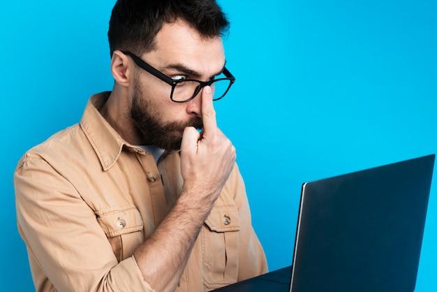 Szokujący mężczyzna patrzeje laptop