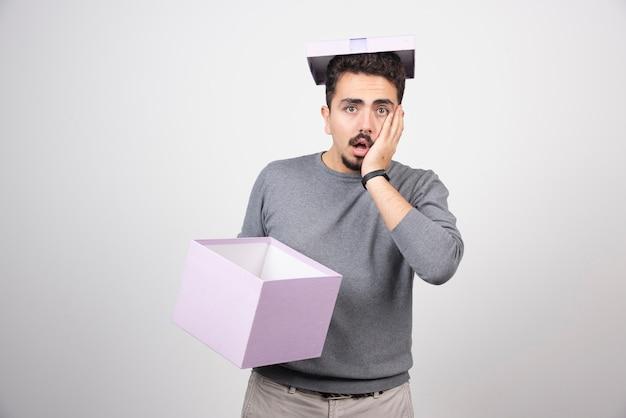 Szokujący mężczyzna trzymający w rękach fioletowe pudełko.