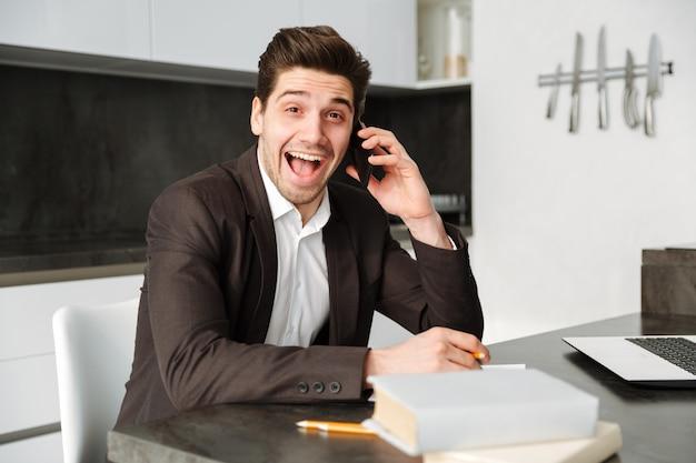 Szokujący młody biznesmen pracuje opowiadać telefonem komórkowym.