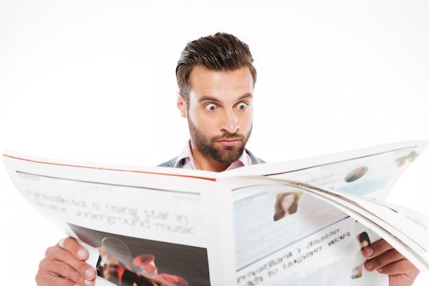 Szokujący młody człowiek czyta gazetę.