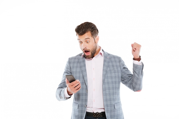Szokujący młody człowiek używa telefon komórkowego.