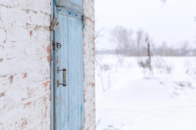 Szopa z niebieskimi drewnianymi drzwiami. zimowy