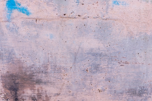 Szorstka betonowa ściana z pociągnięciami farby i pędzla