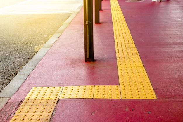 Szorstka, dotykowa nawierzchnia z żółtej kropki dla osób niewidomych na szlaku płytek w japonii, przejście dla osób niewidomych.