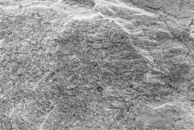 Szorstka, pomalowana ściana w kolorze czarno-białym. niedoskonała płaszczyzna skali szarości. nierówne stare tło dekoracyjne. tekstura czarno-biała. monochromatyczna ozdobna, kamienista powierzchnia