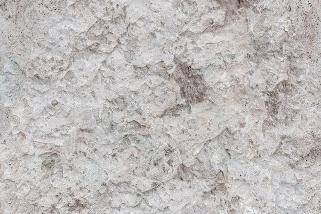 Szorstki, nierówny kamień tekstura szarej betonowej ściany z bliska